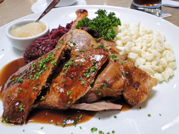 Pato assado servido com repolho roxo, spätzle e purê de maçã