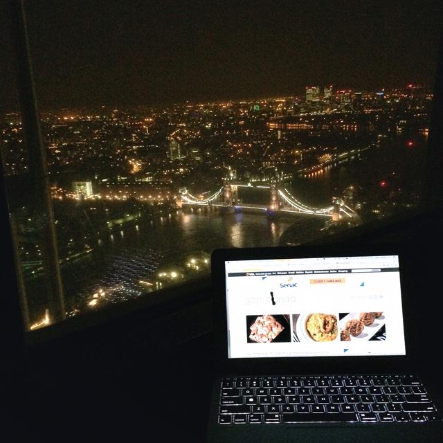 Trabalhando da cama do meu quarto no Shangri-la com Londres iluminada ao fundo...