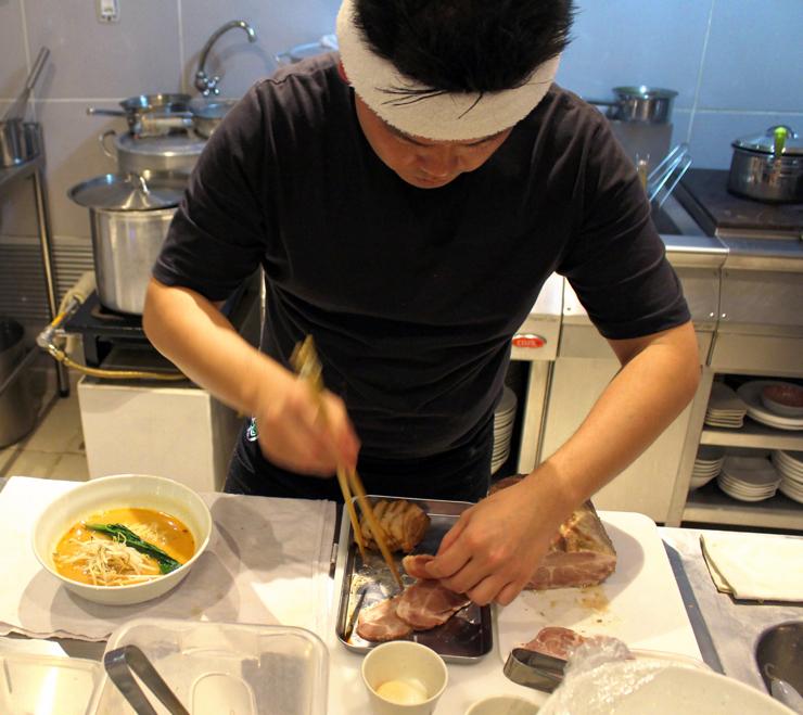 Luis em sua pequena cozinha aberta pro salão no 2nd Floor Noodle Bar