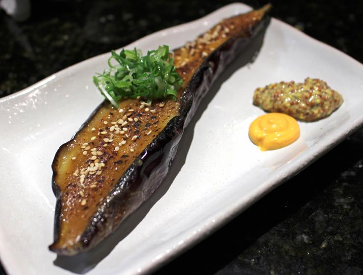 Nasu Dengaku, meia berinjela assada com ama miso, maçaricada na hora de servir e acompanhada por maionese de Siiracha e mostarda Dijon (R$ 18)