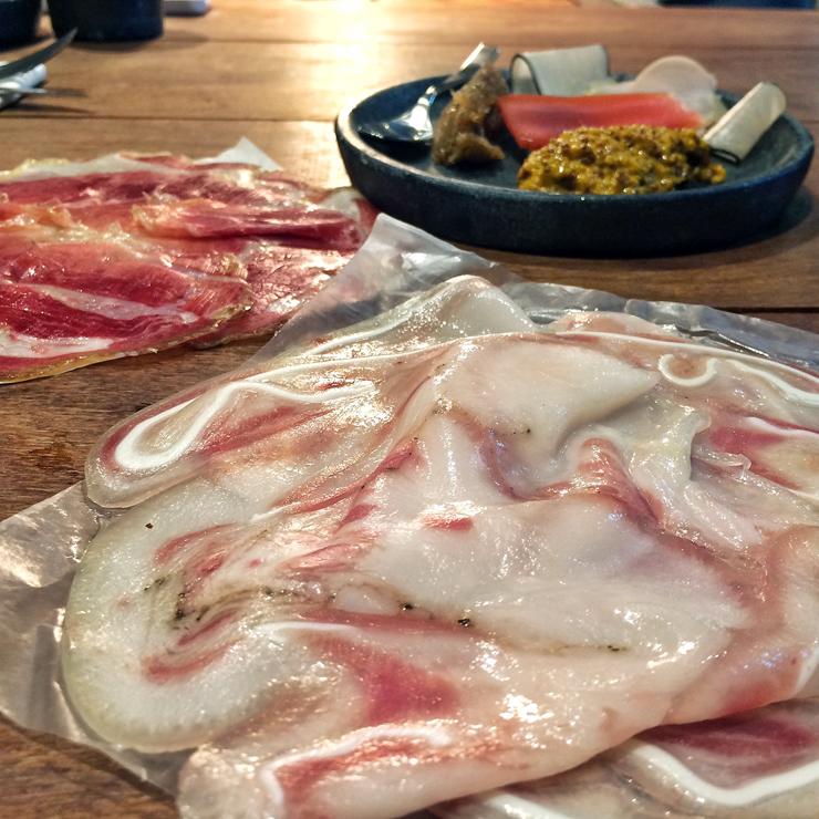 Embutido de cabeça de porco, copa, mostarda fermentada no tucupi, compota de bacon e picles de vegetais.