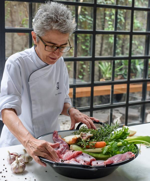 A chef Ana Soares preparando receita com coelho a ser servida em almoço especial no Mesa II