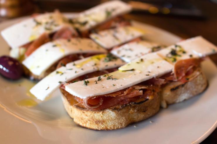 Porções para compartilhar no novo Adeguinha Santiago: Tostada na lenha de queijo de cabra e jamón serrano (R$ 38)