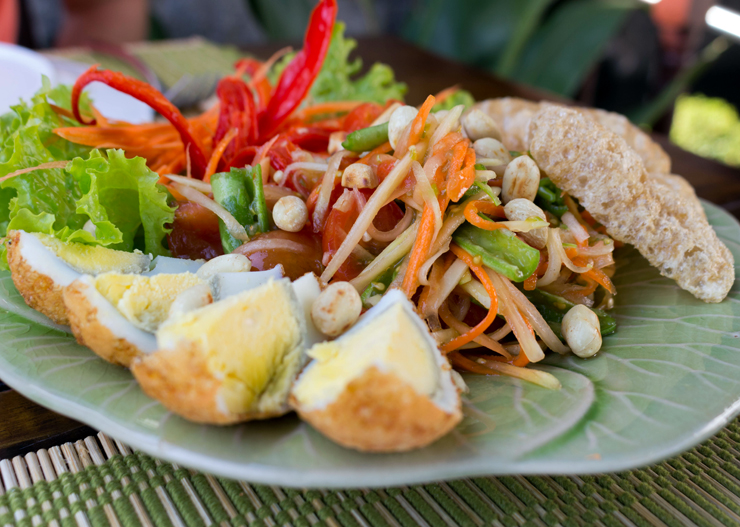 A tradicionalíssima Som Tam, preparada com tiras finas de mamão papaia verde, vagem, lentilha, amendoim torrado, cenoura, ovos cozidos e pimentão ao molho cítrico apimentado