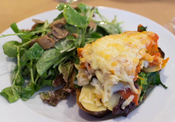 Almoção na Padaria da Esquina: salada de rúcula e cogumelos com Tiborna de bacalhau com espinafre, palmito pupunha, tomate assado, azeitonas e queijo meia cura (R$33)