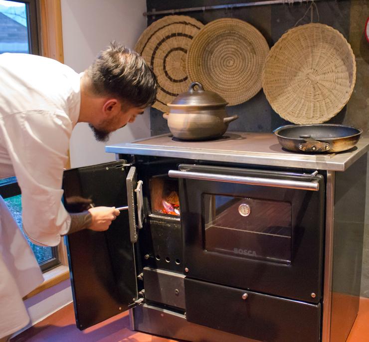 O chef Damian Fernandez acendendo o fogão a lenha para sua aula de culinária - todos os hóspedes podem fazer