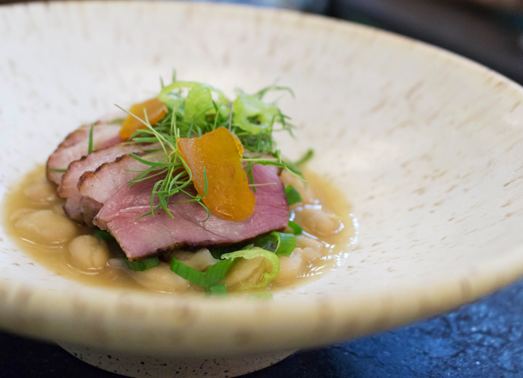 Excelente Peito de pato fatiado sobre feijão branco e botarga do Lilu, do chef Andre Mifano